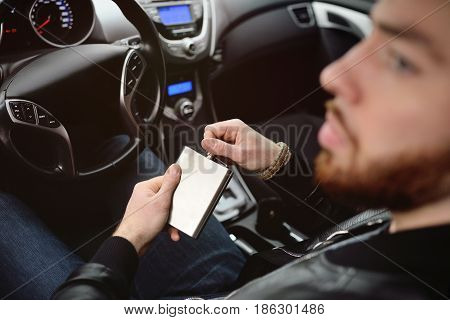 Young man driving a car with an iron flask with alcohol. Danger on the road. Bad habit. Drunk Driver.