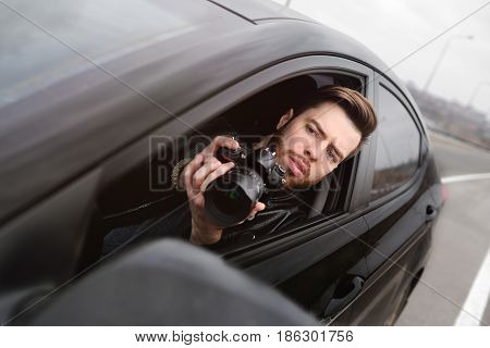The man in the car reviews the photos on the camera. Spy, paparazzi, journalist, photographer.