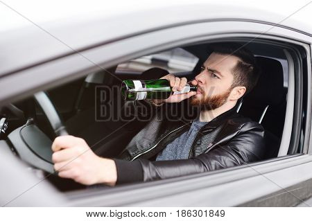 Drunk young man with a beard with a bottle of beer in his hand behind the wheel of a car. Emergency situation, violation of law, drunk driving