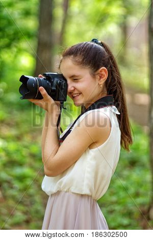Girl is looking trough the lens and make a picture with a dslr camera.