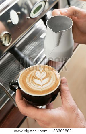 Man holding cup of coffee with latte art
