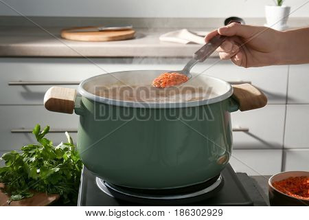 Female hand holding spoon with lentil above pan in kitchen