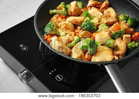 Chicken stir fry with vegetables in pan on electric stove, closeup