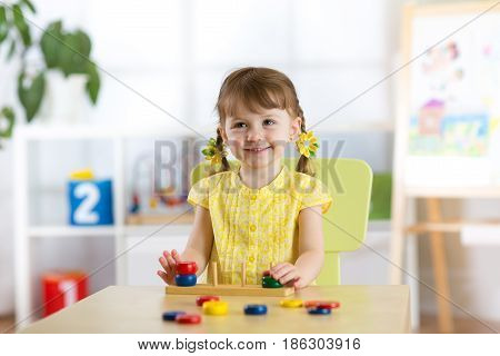 Kid girl playing with logical toy on desk in nursery room or kindergarten. Child arranging and sorting colors and sizes.