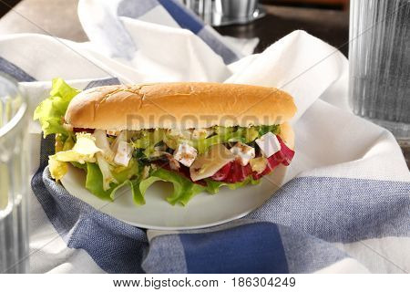 Plate with chicken salad in hot dog bun on table