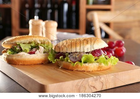 Wooden board with chicken salad in burger buns on table
