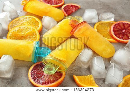 Tasty popsicles with ice cubes and citrus slices, closeup