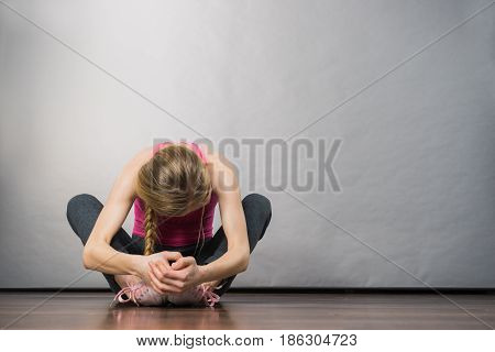 Sad depressed young teenage girl sitting by wall hiding face. School adolescence home violence unwanted love problems.