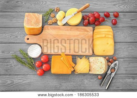 Variety of cheese and nuts around cutting board on wooden background