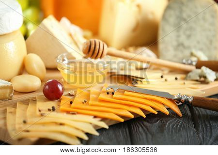 Wooden board with variety of cheese on table