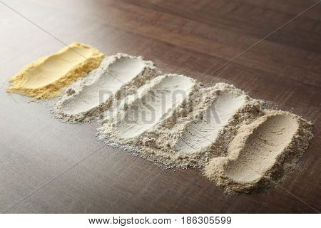 Composition with different types of flour on wooden table