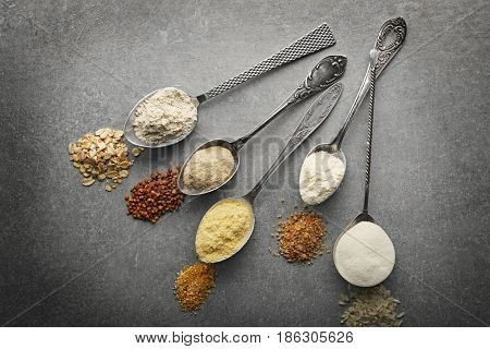 Spoons with different types of flour on grey background