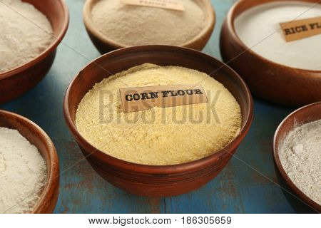 Bowls with different types of flour on grunge wooden background, closeup
