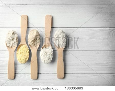 Spoons with different types of flour on light wooden background