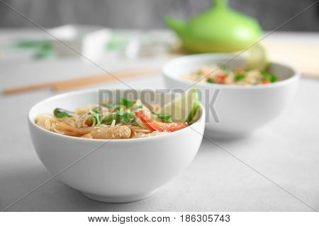 White plate with delicious rice noodle and vegetables against blurred background