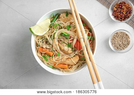 Delicious rice noodle in white plate with spices on light background