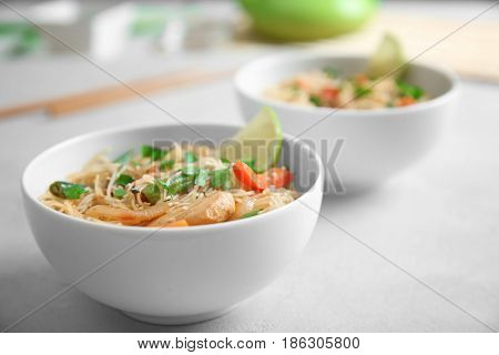 White plate with delicious rice noodle and vegetables on light table