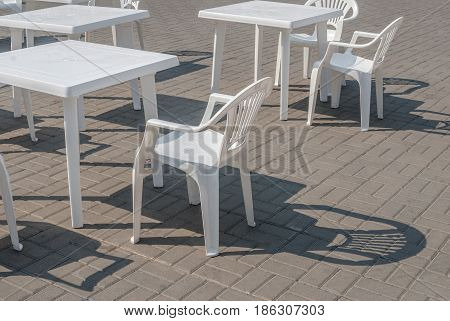 a few plastic chairs and tables on the street, a beautiful sunny day