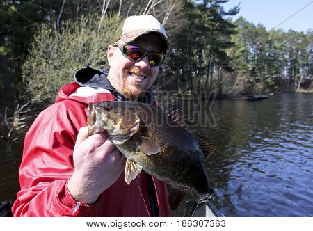 Bass fisherman in a boat holding up a trophy fish