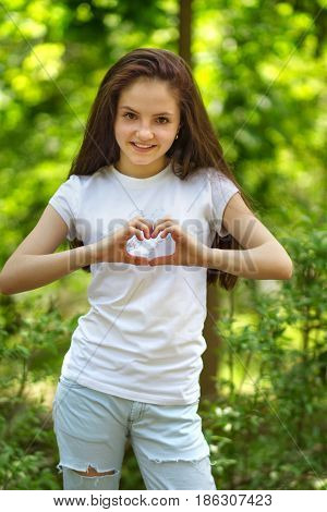 Young girl shows her hands a heart in the park