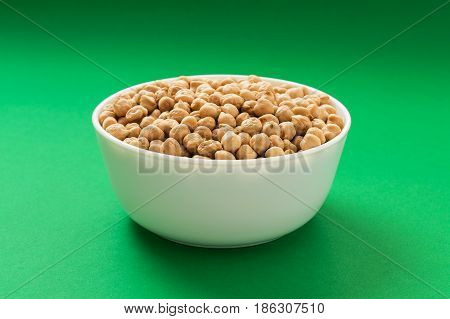 Raw chickpea or garbanzo bean in a bowl on green background. Vegan source of protein.
