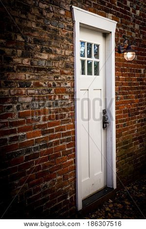 An old fashioned brick wall with door and lamp light.