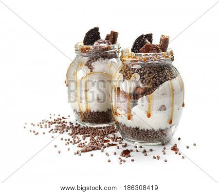 Delicious parfait with chocolate in jars on white background