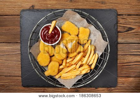 Chicken nuggets and french fries sauces of ketchup and mayonnaise on a black stone background. view from above