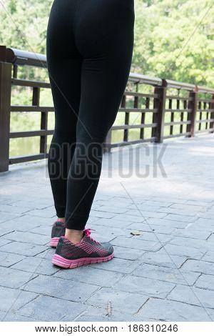 Female Sport Fitness Runner Standing Before Jogging Outdoors On Bridge In Spring Or Summer. Healthy