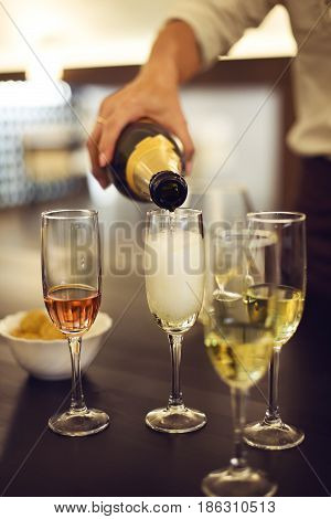 A row of Champagne flutes are being filled on a table and chips