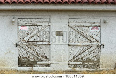 Double doors in an old building are opposite hand mirror images of each other.