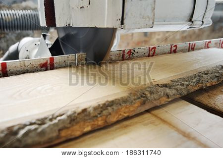 Circular saw saws a wooden beam against the background of the carpentry workshop