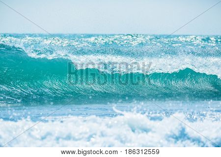 Blue wave in tropical ocean. Wave barrel crashing and sun light