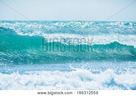 Blue wave in tropical ocean. Wave barrel crashing and sun light