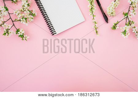 Frame of white flowers, notebook and pen on pink background. Flat lay, top view. Blogger or freelancer desk workspace.