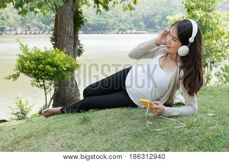 Young Asian Woman Sitting In Fresh Spring Grass Listening To Music On Her Mobile Phone Smiling With