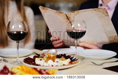 a man with a woman in a restaurant menu background leaf table with food and wine