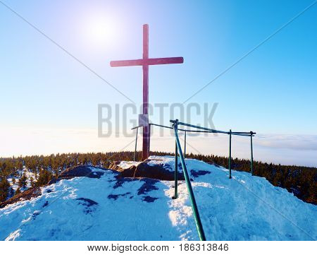 Sharp summit with modest cross raised on mountain peak. Winter daybreak Sun in sky. Wooden unpretentious crucifix in memory of victims of mountains. Vivid photo.