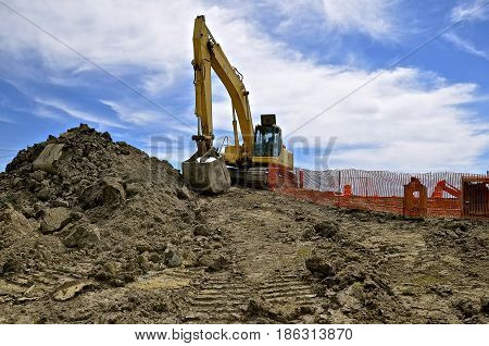 Excavating machine at a road construction site with safety fences surrounding project