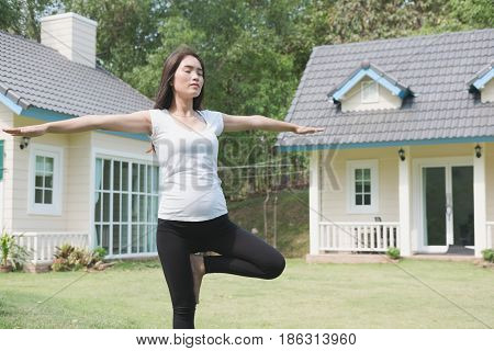 Asian Pregnant Woman Practicing Yoga On Green Grass In Front Of Her House.  Concept Of Prenatal Exer