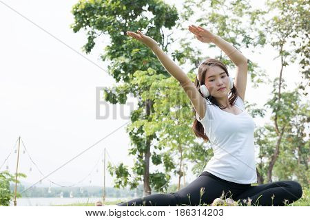 Asian Pregnant Woman Practicing Yoga While Listening To Music On Green Grass In Public Park.  Concep
