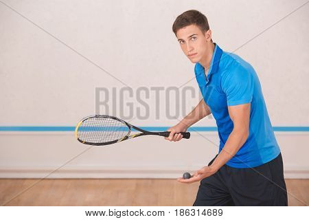 Young brunette man standing in the gym squash game play