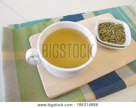 Cup of kukicha green tea and tea twigs, stems and stalks