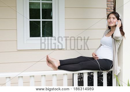 Young Asian Woman Sitting On Balcony Listening To Music Smiling With Pleasure. Beautiful Female Expe