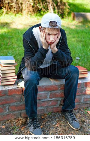 Sad Teenager with the Books in the Park