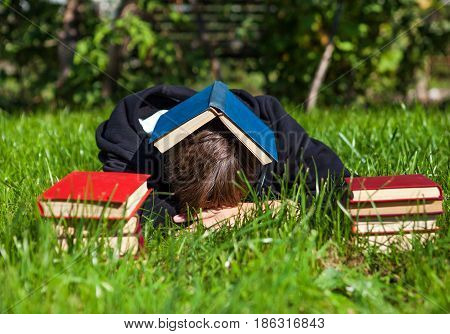 Person sleep with a Books on the Summer Meadow