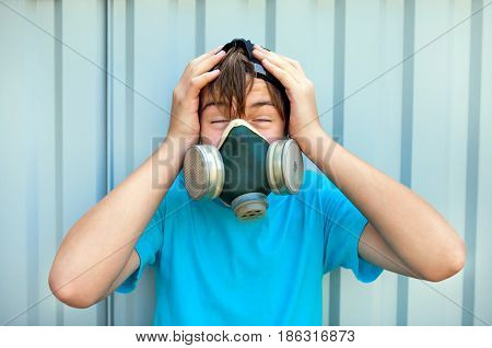 Teenager Portrait in the Gas Mask on the Wall Background