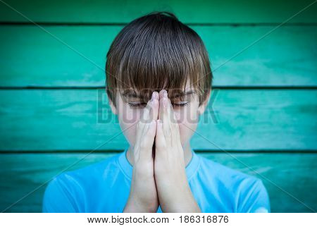 Vignetting Photo of Teenager praying on the Wooden Wall Background