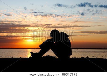 Sad Teenager Silhouette at the Sunset Background