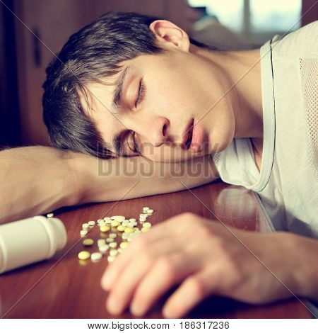 Toned Photo of Young Man sleep on the Table near the Pills
